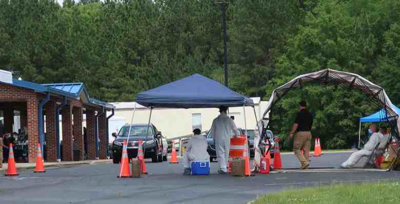 we see several tents with cars lined up waiting for people inside to be tested for COVID-19