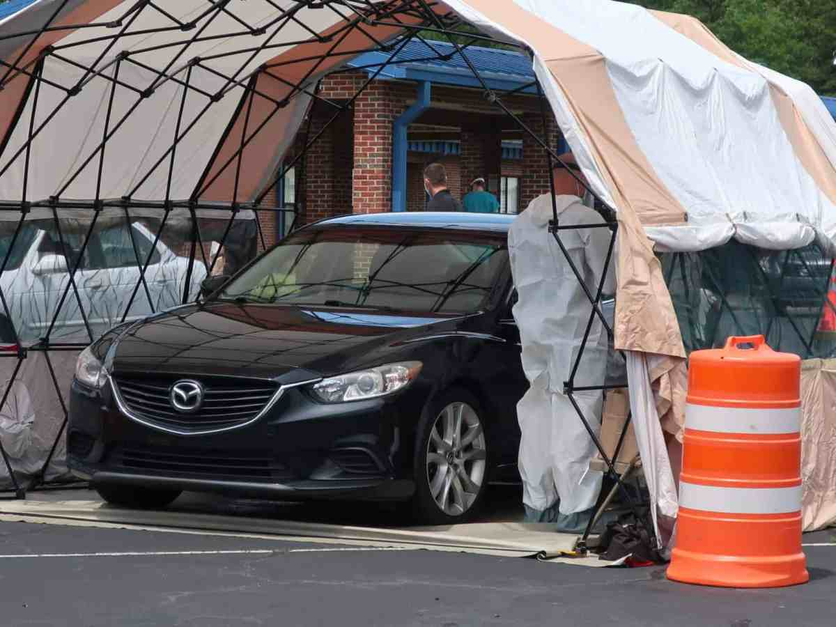 We see a tent with several people in it who are wearing head-to-toe personal protective equipment, thyr'e talking to someone in a car who is waiting to b tested for COVID-19