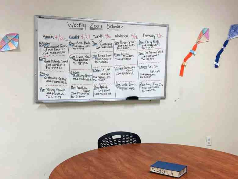 white board with a meeting schedule in a common area