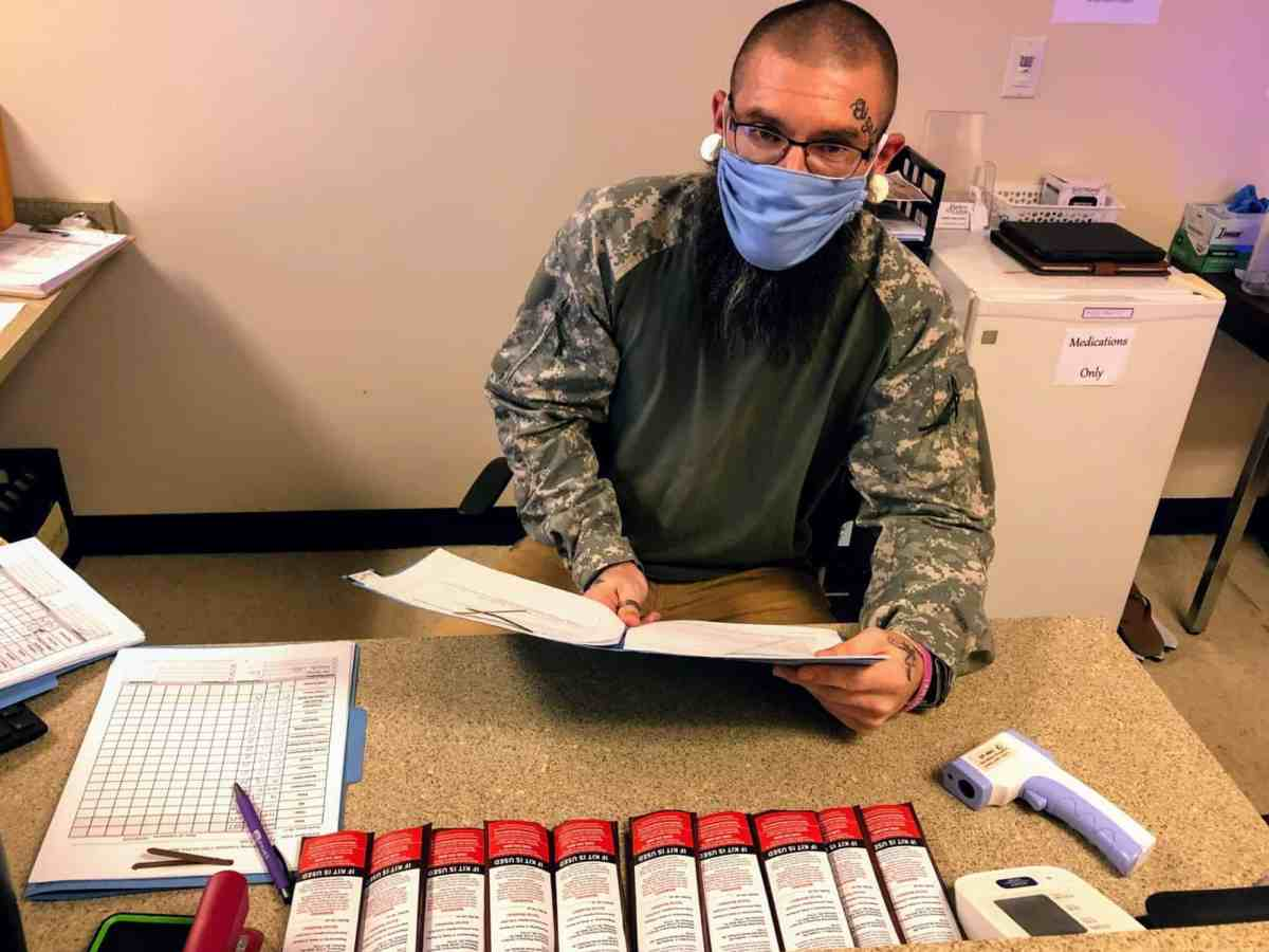 man wearing mask sits behind desk with naloxone kits in a line in front of him