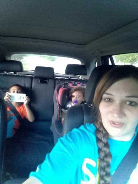 shows a woman in a minivan taking a photo into the back seat where her two children are sitting in car seats.