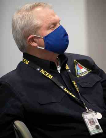 shows an older white man wearing a mask to prevent transmission of COVID-19