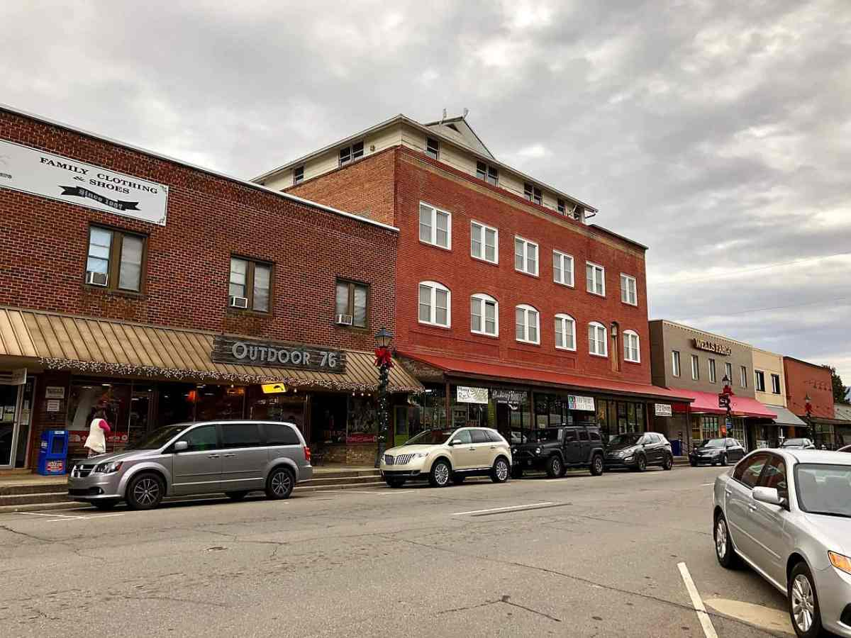 Photo shows Franklin, NC, a town in Macon County experiencing a coronavirus outbreak. Red brick buildings, a classic main street scene, set against a grey sky.