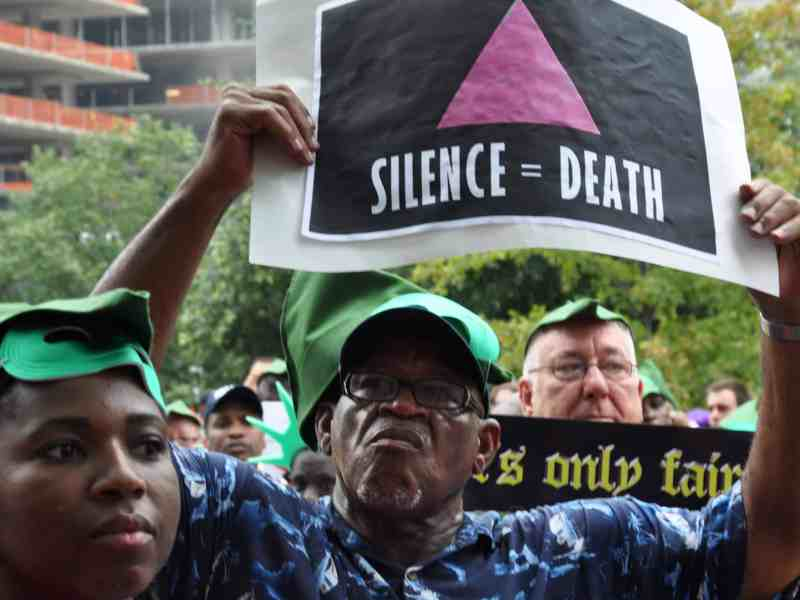 """An older black man holds a black sign with a pink triangle and the words, """"Silence = Death,"""" below it at The AIDS Coalition to Unleash Power, or ACT UP, 25th anniversary march in New York City in 2012."""