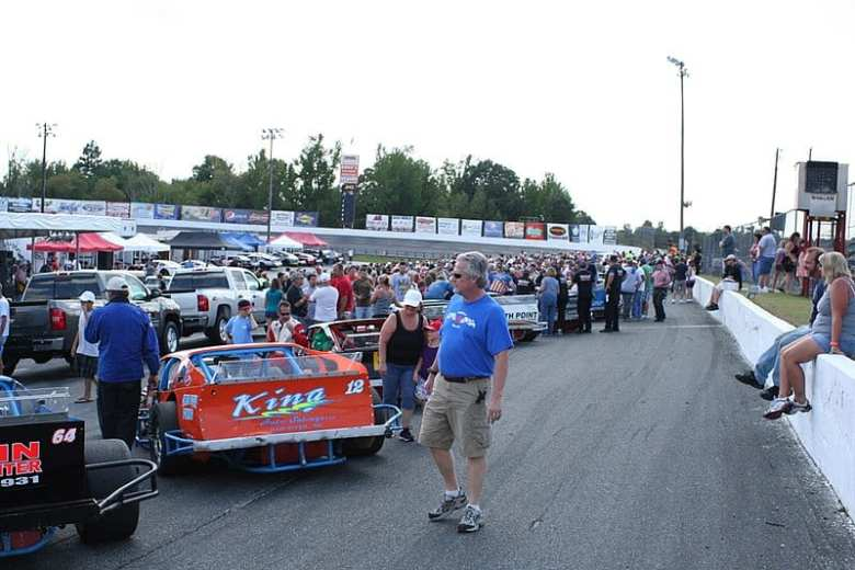 Shows a crowd of people looking at race cars in an outdoor venue