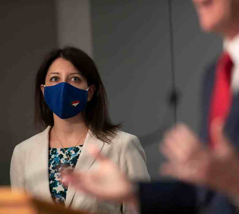 shows hands of a speaker in the foreground, a woman in the background looks at the person speaking. She's wearing a mask against covid-19