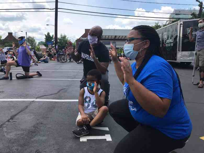 A black family of mother, father and little boy kneels during a demonstration against racism in Chapel hill