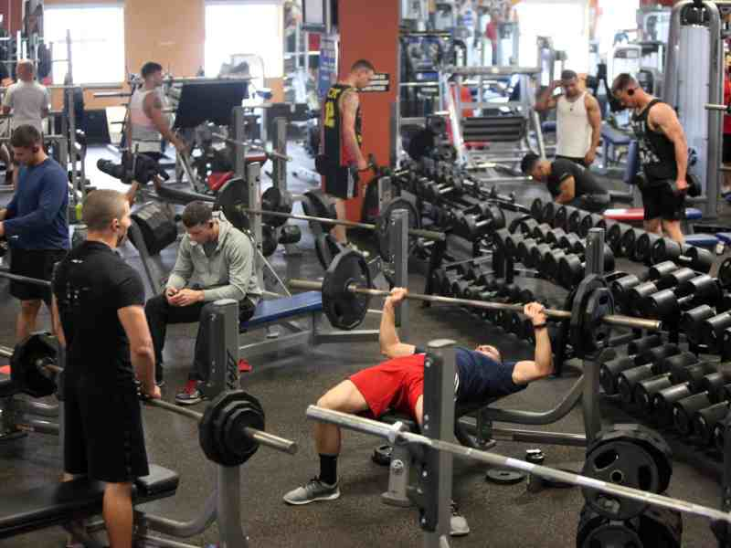 shows men working out in a crowded gym with many freeweights.