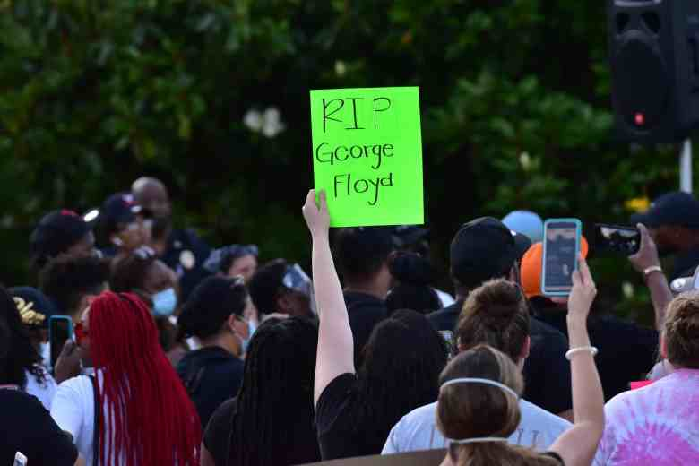 """People gather, on person holds up a sign that reads """"RIP George Floyd"""" above the crowd. Many masks to protect themselves and others from COVID-19 are visible in the crowd."""