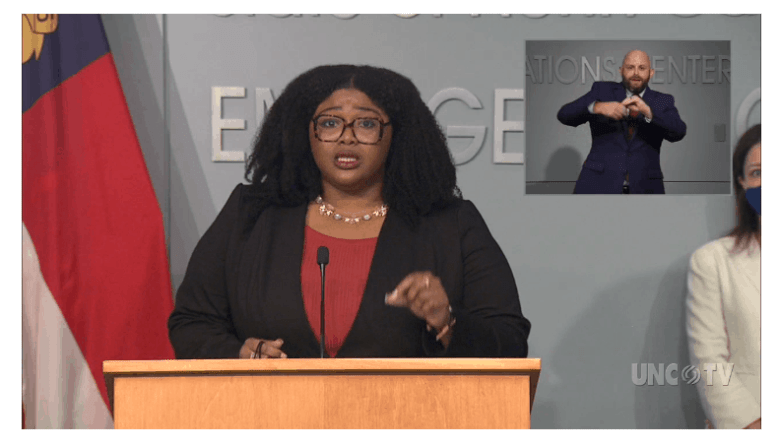 shows a woman standing at a podium, there's another woman behind her wearing a mask against COVID-19