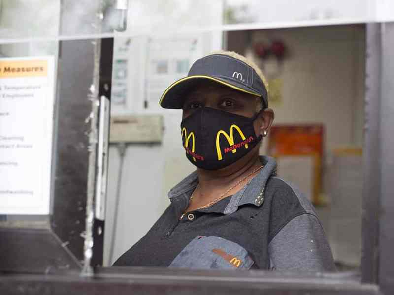 Shows a woman in a McDonald's takeout window wearing a branded mask against COVID