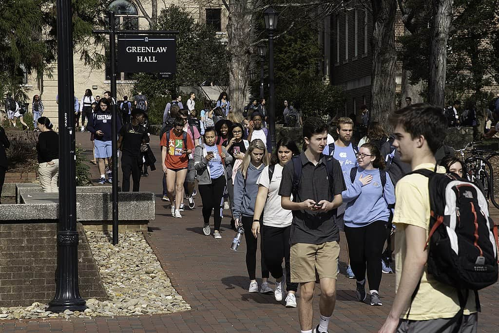 shows a group of students, many in Carolina blue, walking on the brick pathways of UNC Chapel Hill
