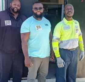 photo shows three Black men standing in a row and smiling