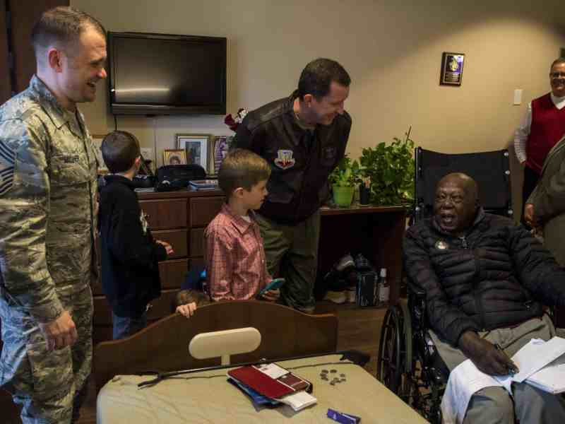 shows people in military uniforms talking to an aging veteran who's in a wheelchair, they're all smiling and laughing.
