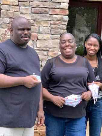 image shows a family of three, all dressed in black, holding white facemasks and smiling