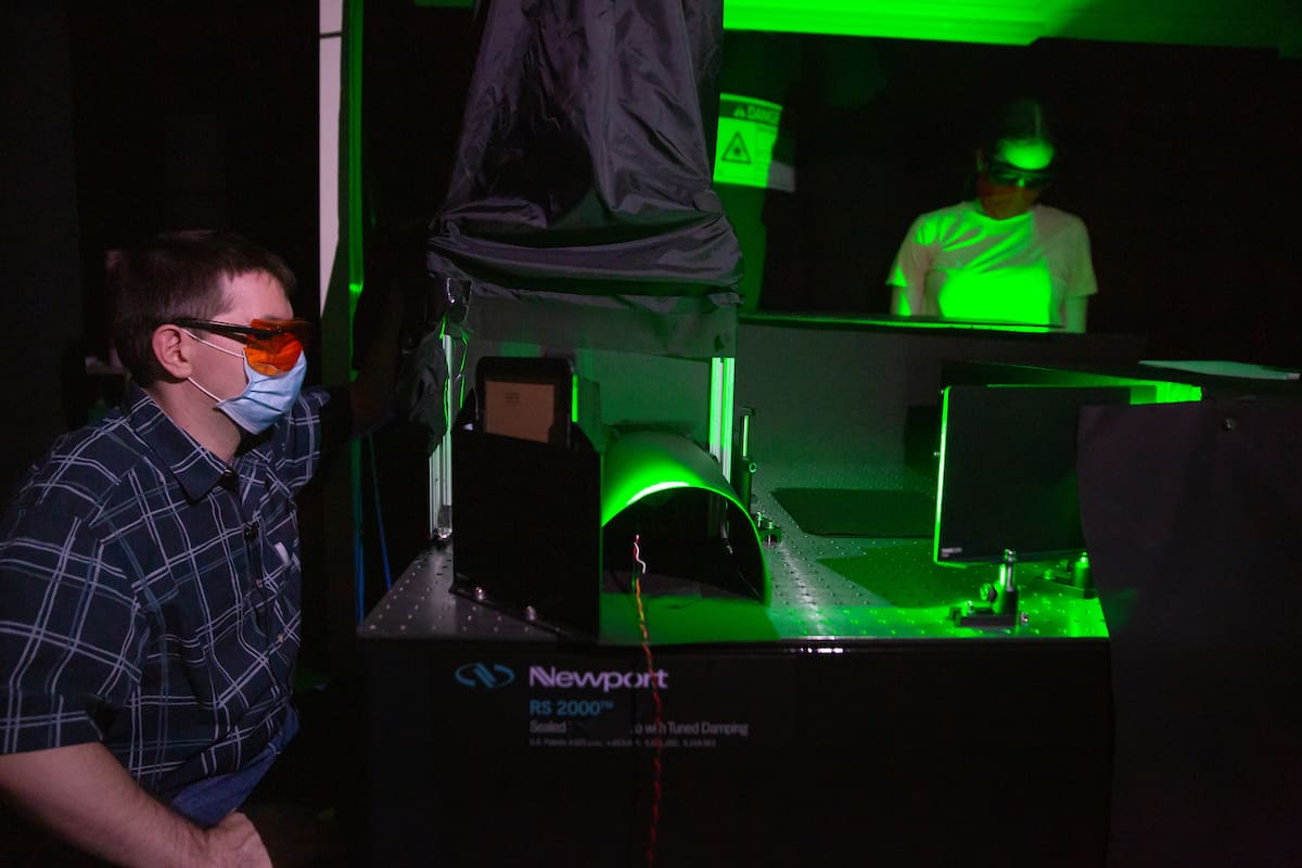 shows a man in a mask sitting next to electronic equipment that's glowing green.