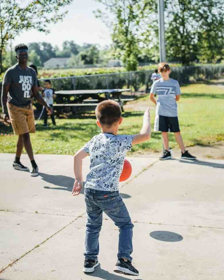 photo shows a small boy in a t-shirt and blue jeans bouncing a red ball with another boy and a counselor in a driveway