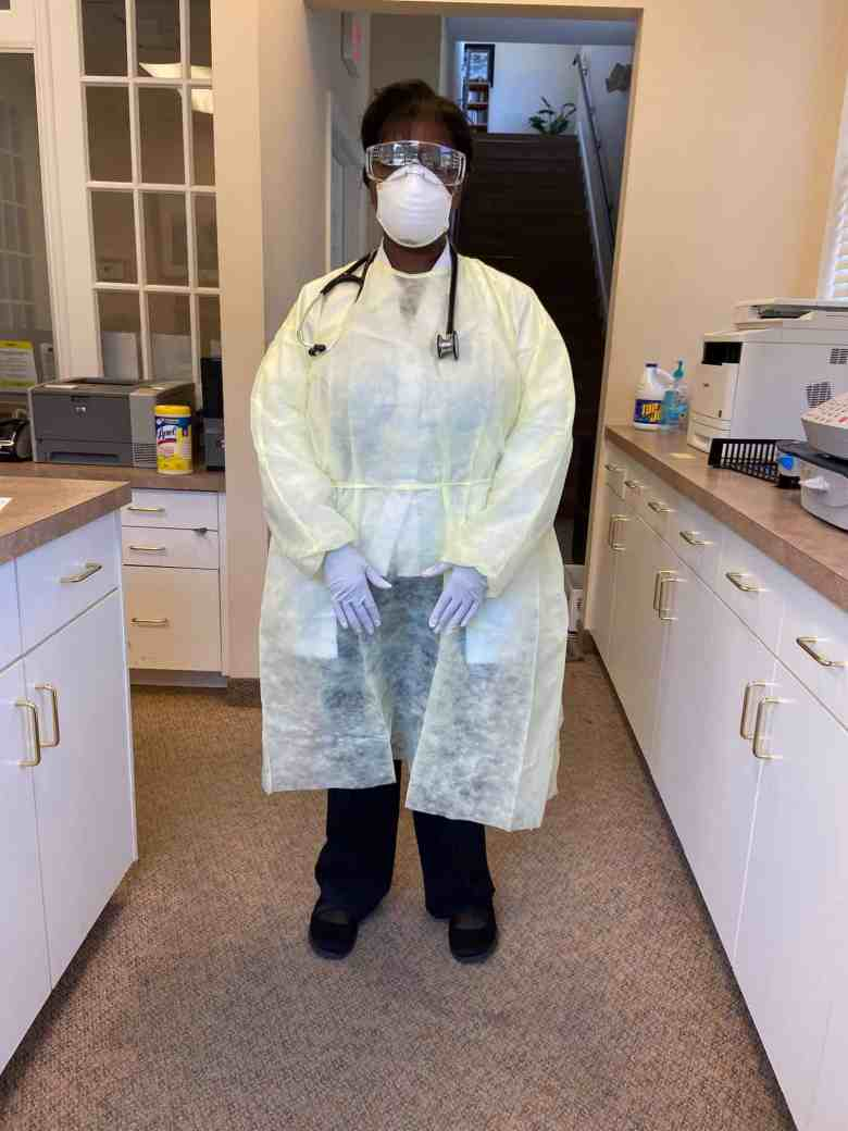 shows a woman who is wearing a gown, gloves, mask and goggles, to prevent being infected by COVID