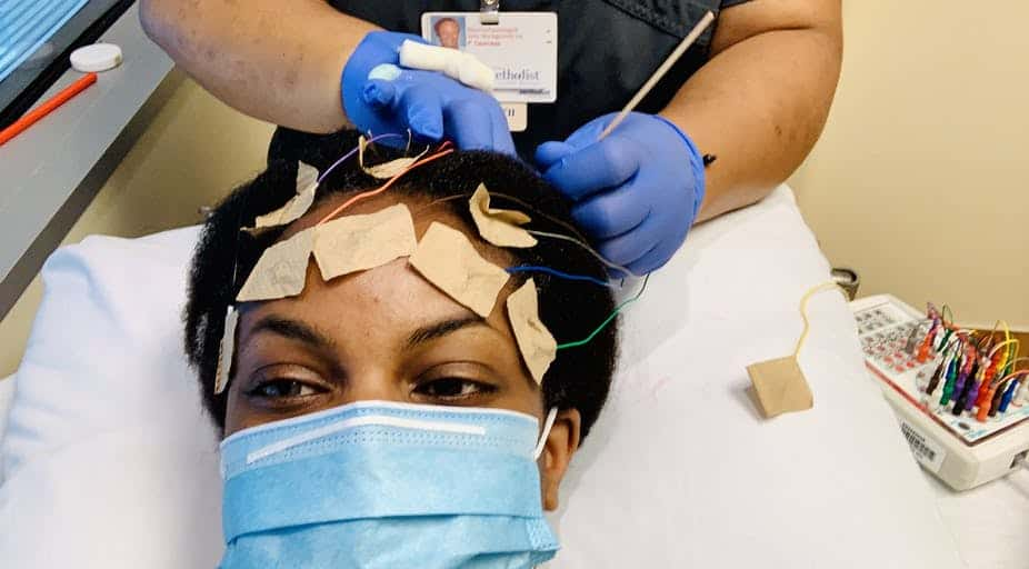 shows a woman with a mask having electrodes stuck to her head to test for neurological effects of COVID-19