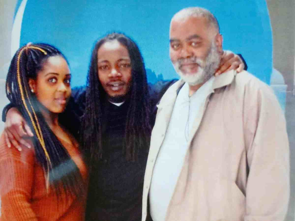 We see Robert Thomas Senior, 59, smiling at the camera. His son Robert Thomas Junior, 30, stands in the middle of the frame with his arm around his father and another young woman in orange.