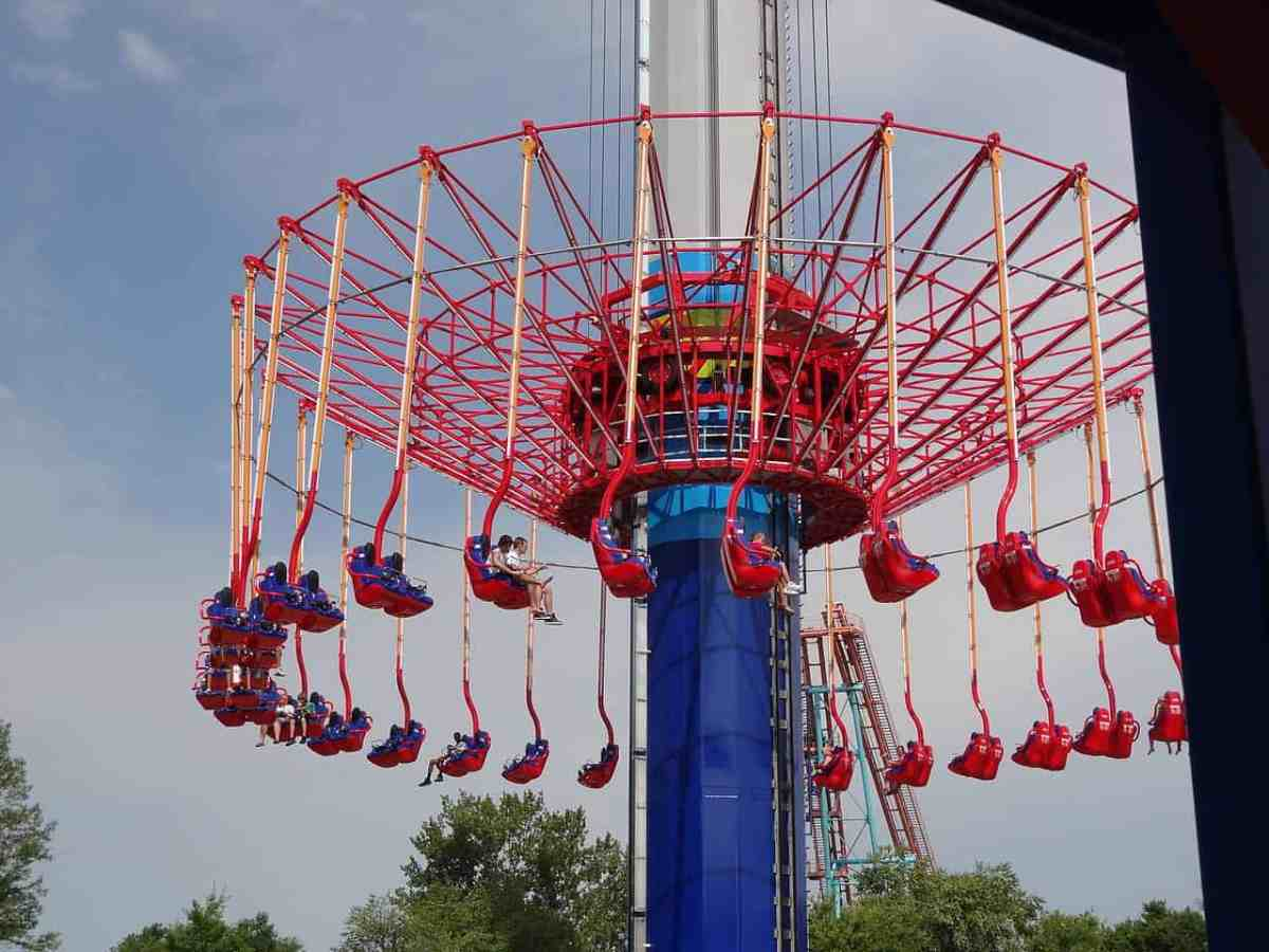 """Shows the brightly colored """"windseeker"""" ride at Carowinds, where red seats suspended from a blue column swirl high in the air."""