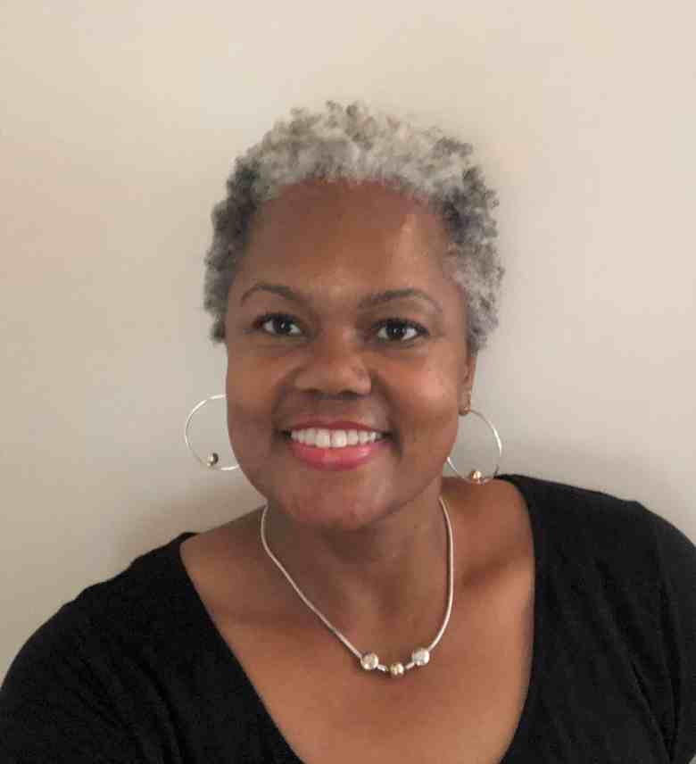 We see Noshima Darden-Tabb smiling at the camera for a headshot. Darden-Tabb, who is Black and has a pixie-cut of salt-and-pepper hair, wears silver hoop earrings, a matching necklace, and a black scoop-neck shirt.
