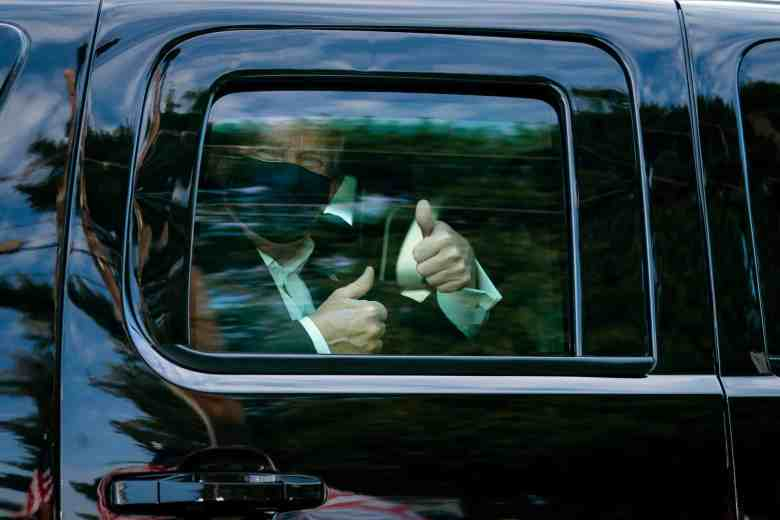 photo shows the closed window of a black car, and a masked President Trump giving a thumbs up inside