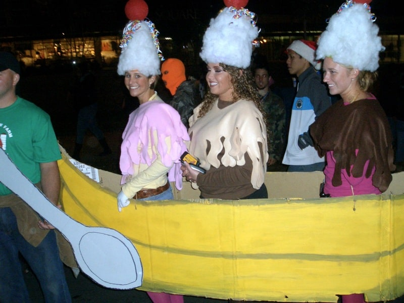 three girls are dressed as a banana split - complete with a large yellow banana made out of carboard that goes around all three of them and tall white hats that look like whipped cream