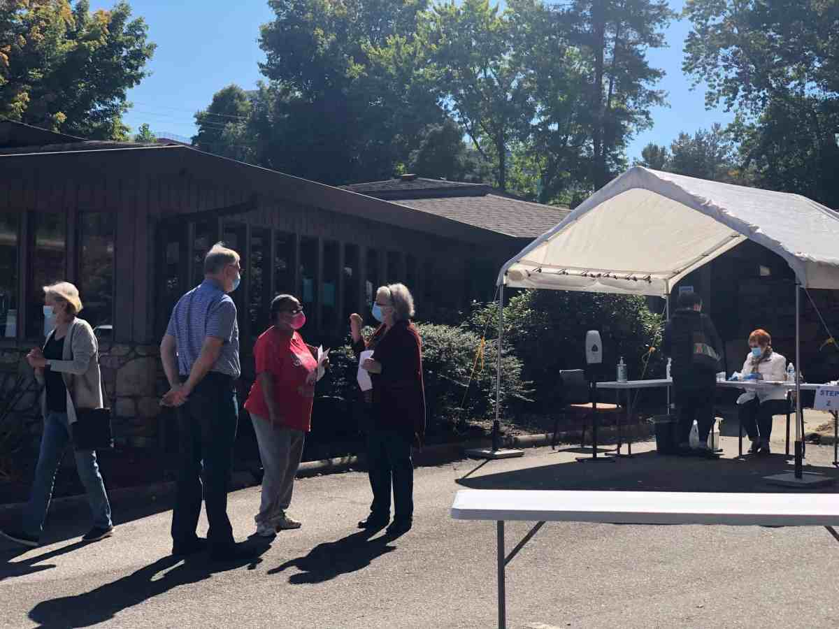 photo shows three older people with masks standing and talking outside a white tent where someone else sits ready to help with voting