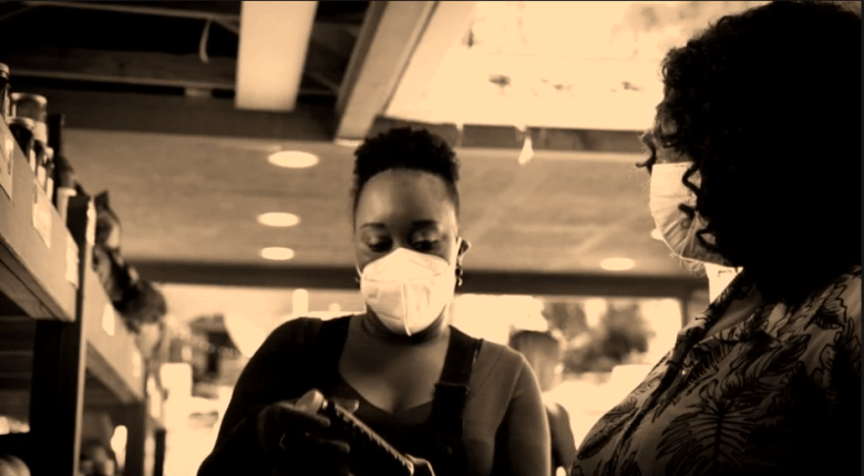 Sepia tone image of a young Black woman wearing a mask against COVID in a store talking with another woman, who's also wearing a mask