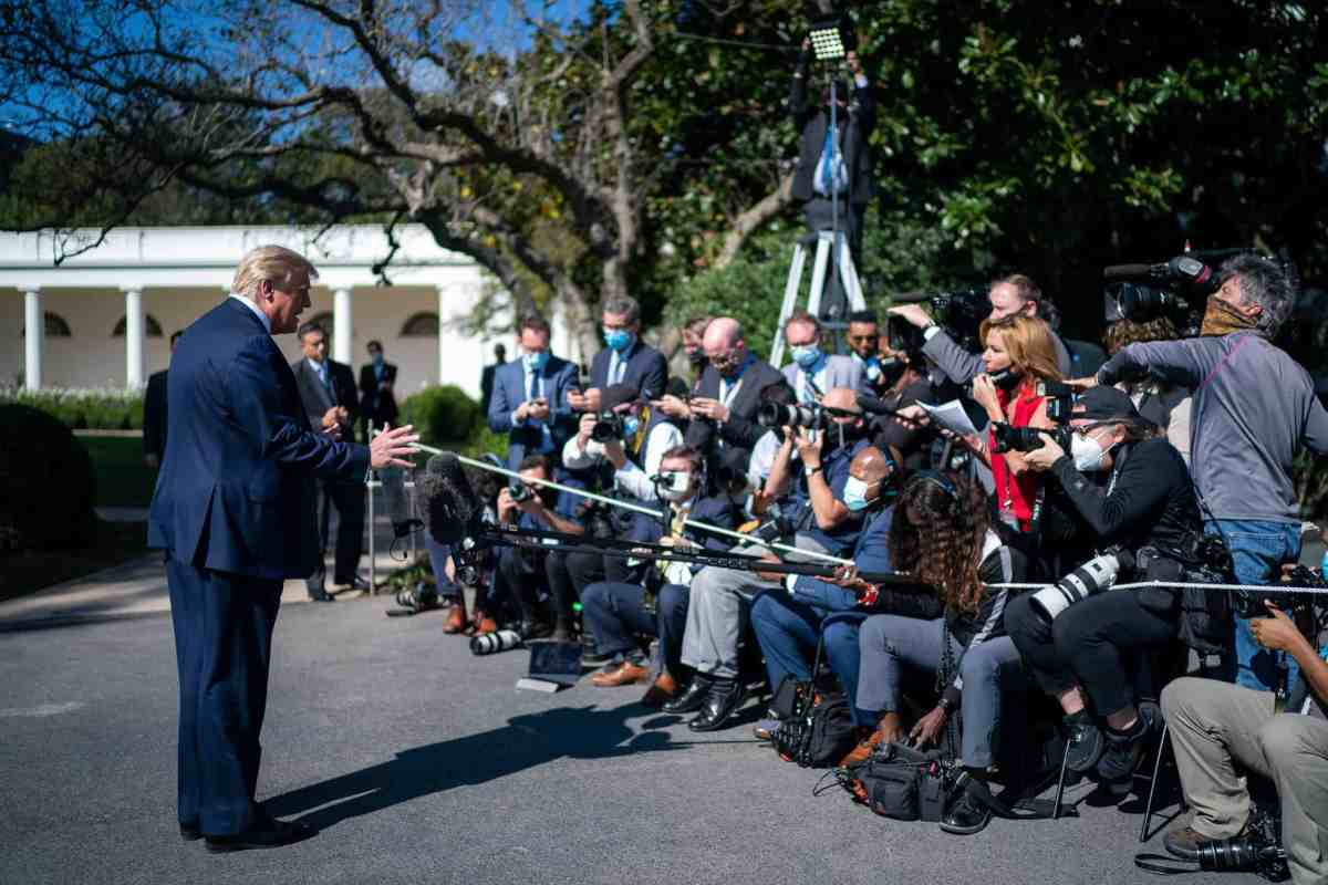 shows president trump without a mask talking to mmbrs of the media who are gathered behind a rope, they're all wearing masks, he is not. He was diagnosed with COVID-19 on the morning of Oct 2