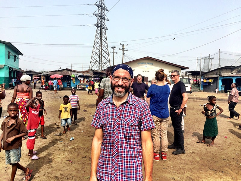shows a man in a kerchief standing in an African marketplace, smiling at the camera