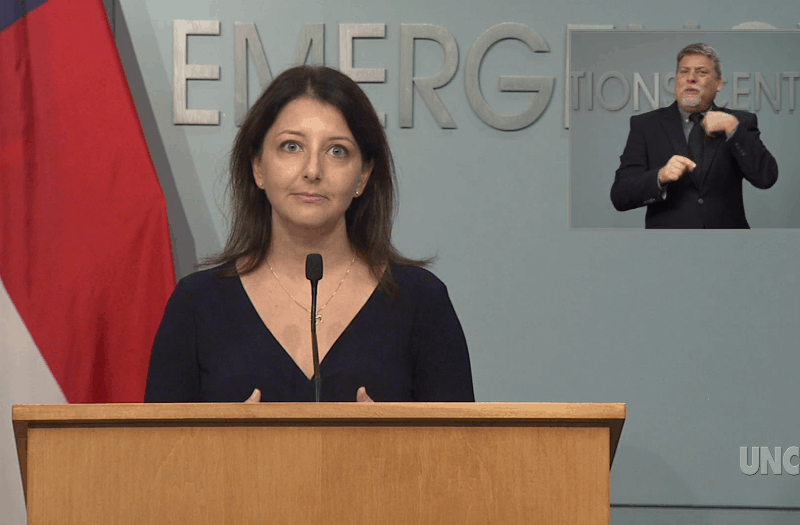 Shows a brunette woman in a dark dress standing at a podium, with a grim, determined look on her face as she looks at the camera. She's worried about the state of North Carolina's COVID outbreak. IN the upper right hand corner, a sign language interpreter gestures with his hands.