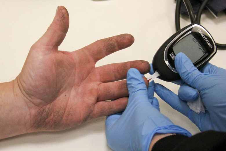 A closeup of a hand getting blood sugar checked.
