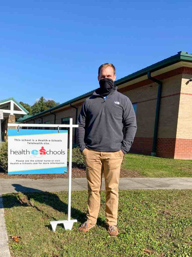 Shows a man smiling behind a mask worn to prevent transmission of COVID-19. He's standing next to a sign for the Health-e Schools sign for a clinic site at Greenlee School.