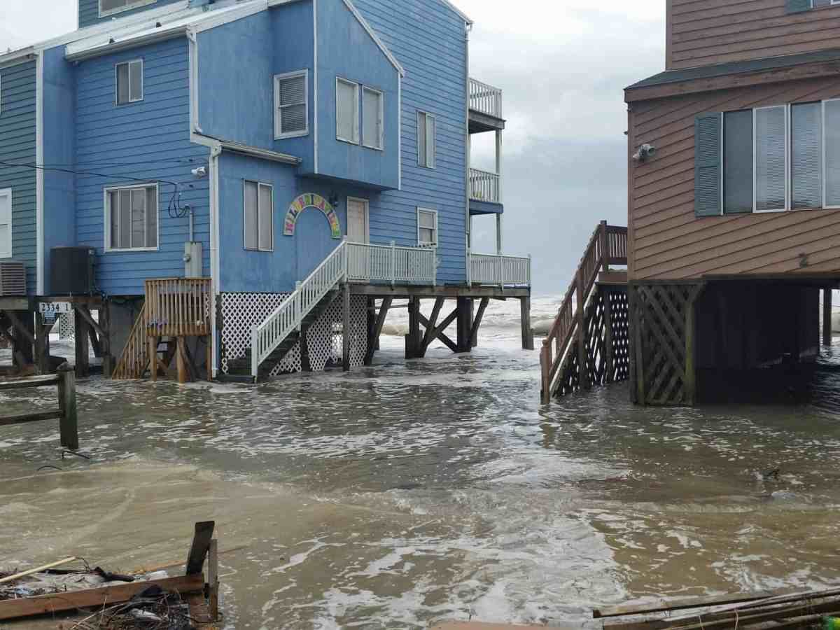 photo shows two houses on stilts in the outer banks with feet of water below them