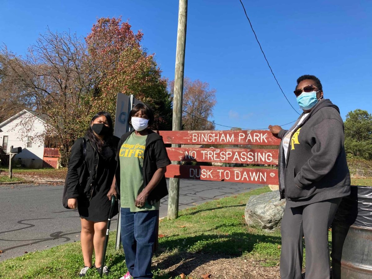 Cottage Grove activists, from left, Sel MPang, Verna Torain and Patricia Macfoy stand beside the sign for Bingham Park. Photo credit: Greg Barnes