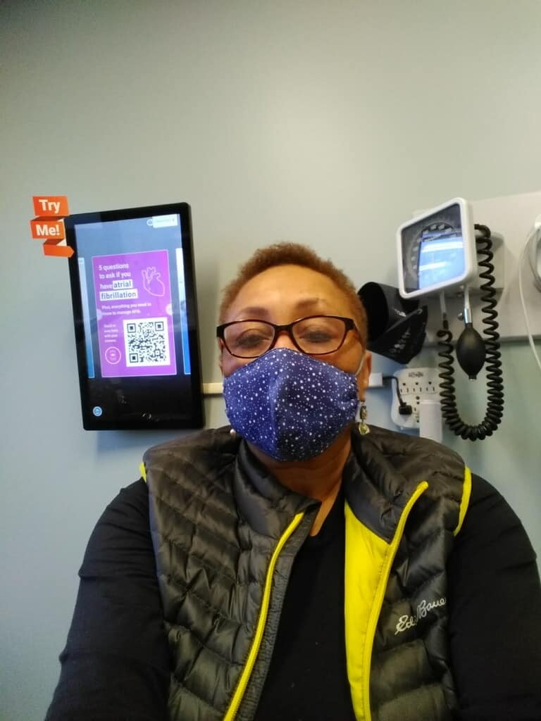 photo shows Melba, a Black woman in a purple mask, glasses and a yellow and black vest, sitting in front of exam room equipment