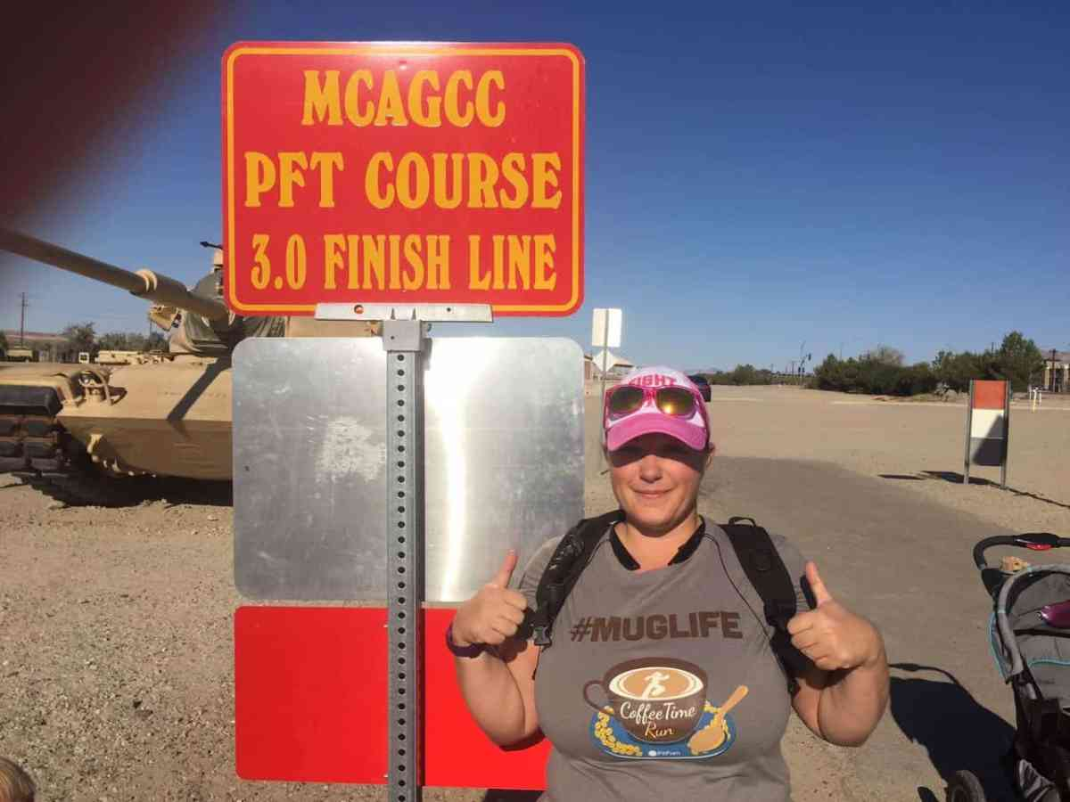 A woman a hat and thumbs up at a race in the desert.