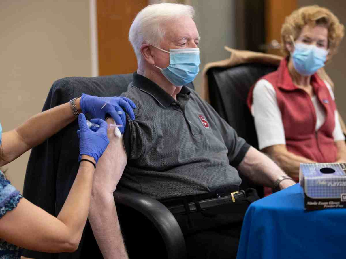 shows a woman in medical gloves giving an injection to an older man, while an older woman looks on. They're all wearing masks to prevent transmission of COVID-19.