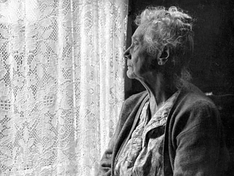 photo shows an elderly woman in a dress and cardigan looking out a window covered by a lace curtain