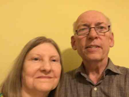 We see a slightly-shaky picture of two elderly white people smiling at the camera in front of a yellow background.