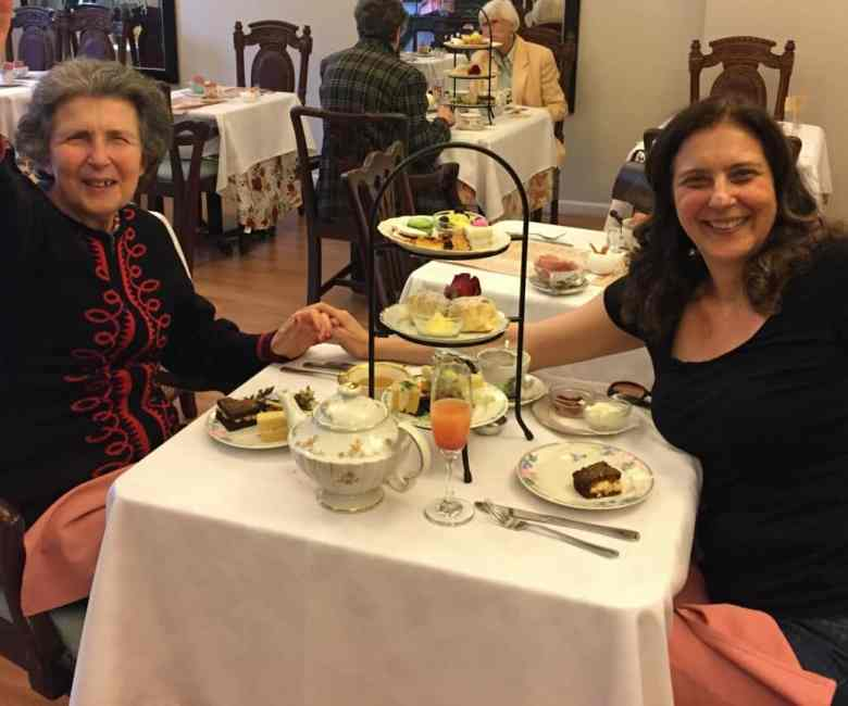 We see Barbara Fischer, 83, eating dessert while holding hands with her daughter Ester Amy across the table at her assisted living facility.
