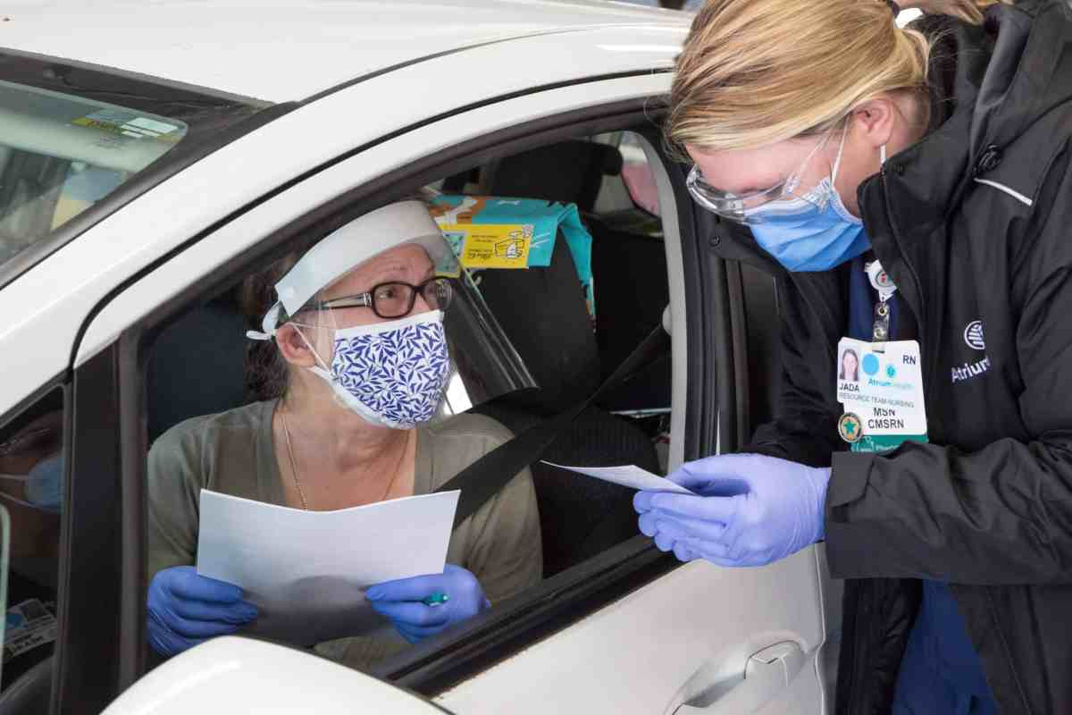 An older woman wearing a mask and face shield sits in the front seat of a passenger vehicle holding papers and talking to an RN who will be giving her a COVID vaccine shot.