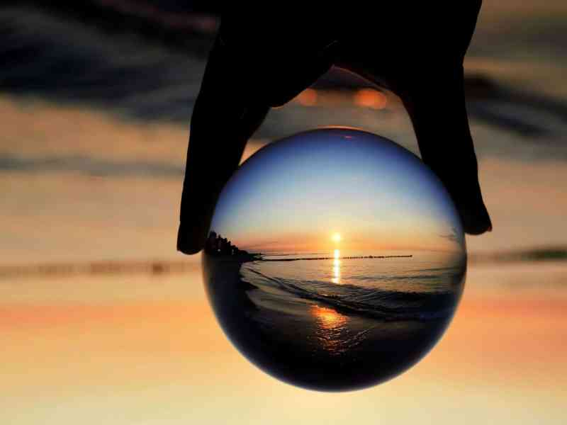 a hand holds a glass globe, flipping the reflection of a sunset over the beach