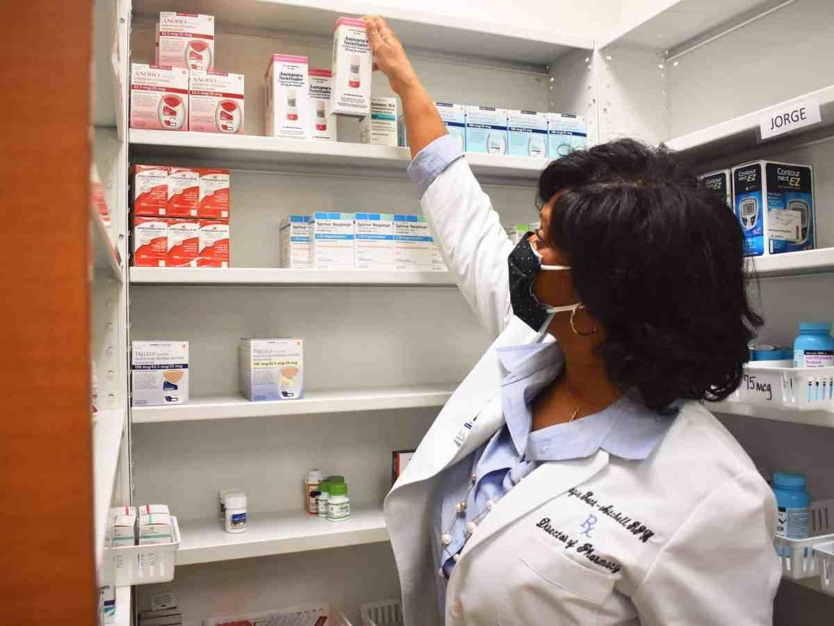A pharmacist in a white coat grabs an asthma inhaler