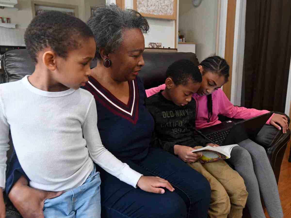 shows an older Black woman with three young children on a couch, the kids are reading