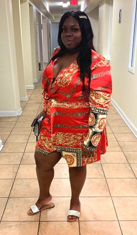 A woman in a striking red dress stands in a hallway. She's Jamesha Waddell, a 23-year old college student who died of coronavirus last year.