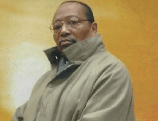 We see Fabian Tinsley looking at the camera while wearing glasses and a tan trench coat. Tinsley, who is Black, has the beginnings of the goatee in the photo, and looks solemnly at the camera.