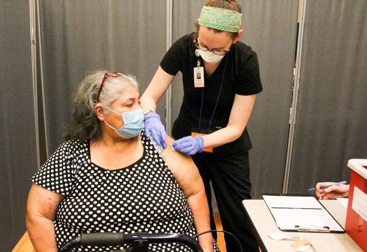 An older woman in graying hair is wearing a mask as a nurse prepares to give her a coronavirus vaccine at a temporary clinic in Asheville.